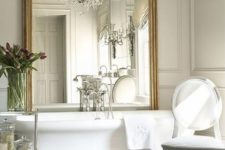 12 an oversized vintage frame mirror and a large crystal chandelier over the tub can be a glam statement