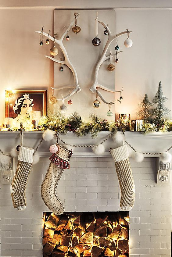 some stockings, an evergreen garland with lights, candles and antlers with Christmas ornaments