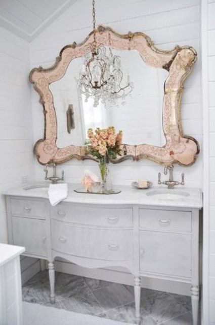 a large mirror in a unique vitnage frame with a metal touch brings chic and glam