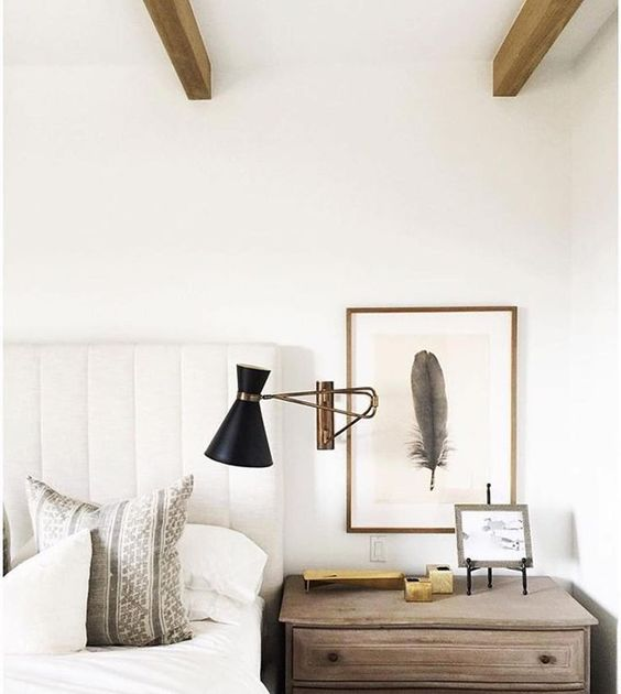 a large sconce with a metallic base and a black lampshade to make a statement