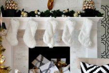 13 a shiny glam mantel with faux fur stockings, Christmas ornament trees and gifts inside the fireplace