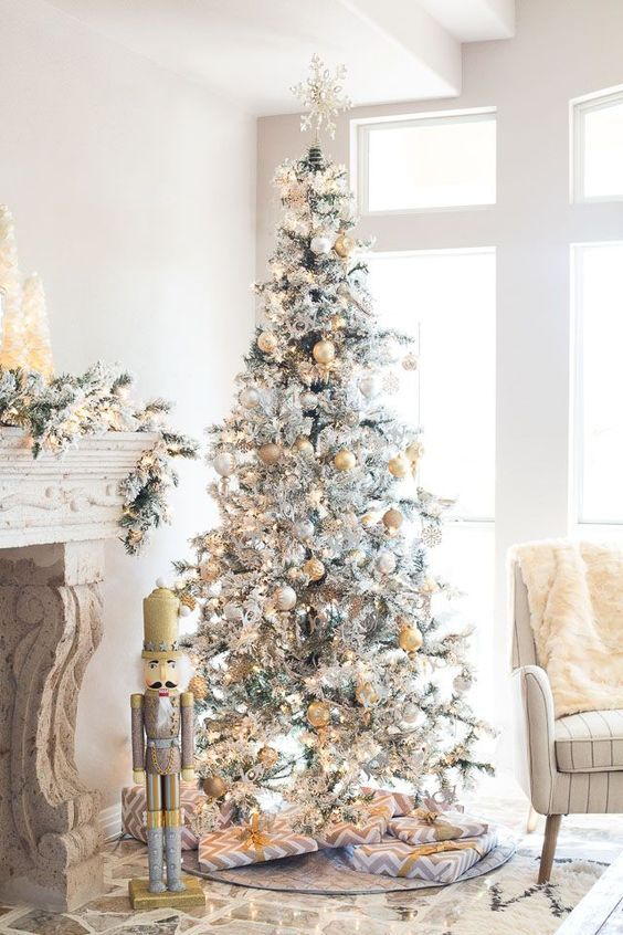 a snowy Christmas tree with gold and silver ornaments and a snowflake on top looks glam