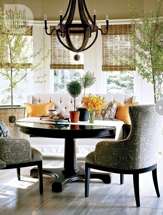 a stylish breakfast or dining zone with upholstered furniture and a round pedestal table with a traditional feel