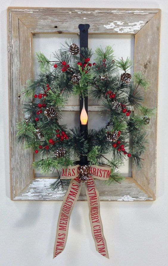a window frame wreath of faux evergreens, berries and pinecones with a burlap bow and a light