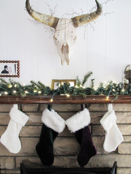 an evergreen garland with lights and some faux fur stockings hanging on the mantel