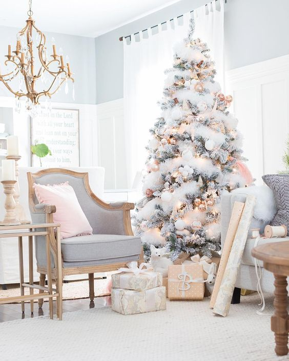 a flocked tree with gold and copper Christmas ornaments and shiny touches