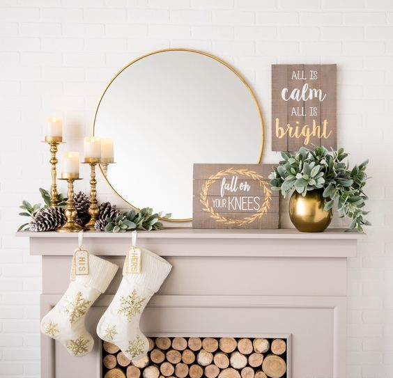 a glam and rustic Christmas mantel with large pinecones, gilded candle holders and a vase, a sign and a mirror