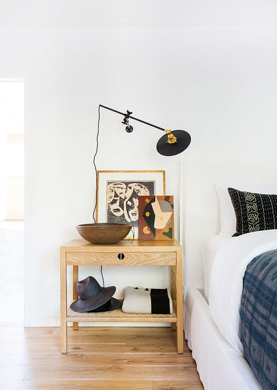a super creative wall sconce on a long black leg to rotate it however you want and use it in an eclectic bedroom