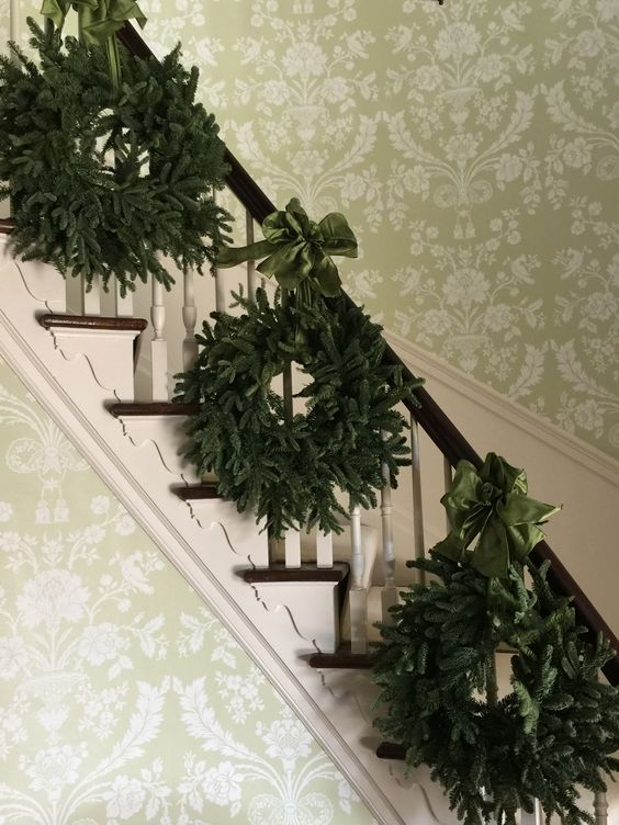 a trio of evergreen wreaths with emerald ribbon bows for decorating stairs