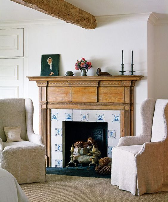 the fireplace is clad with blue and white tiles and wood in a seaside room