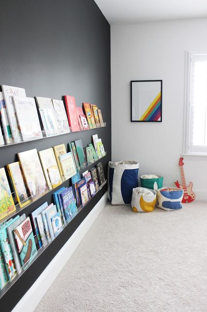 a black statement wall with lots of colorful books on display attract attention to them