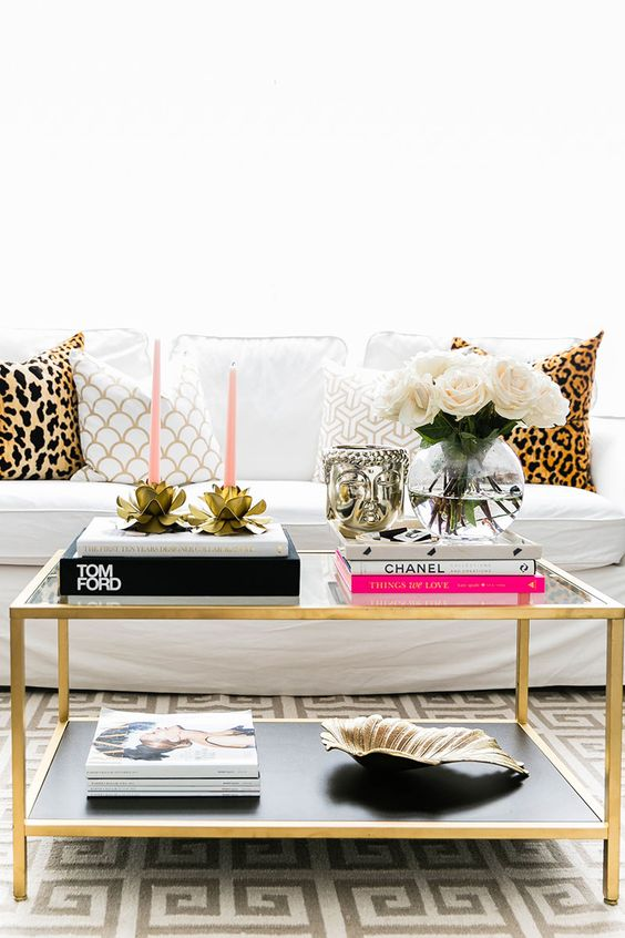 a chic brass coffee table and leopard pillows add glam to the space