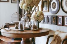 15 a large rustic wooden pedestal table with a fall display and a galery wall on the stairs