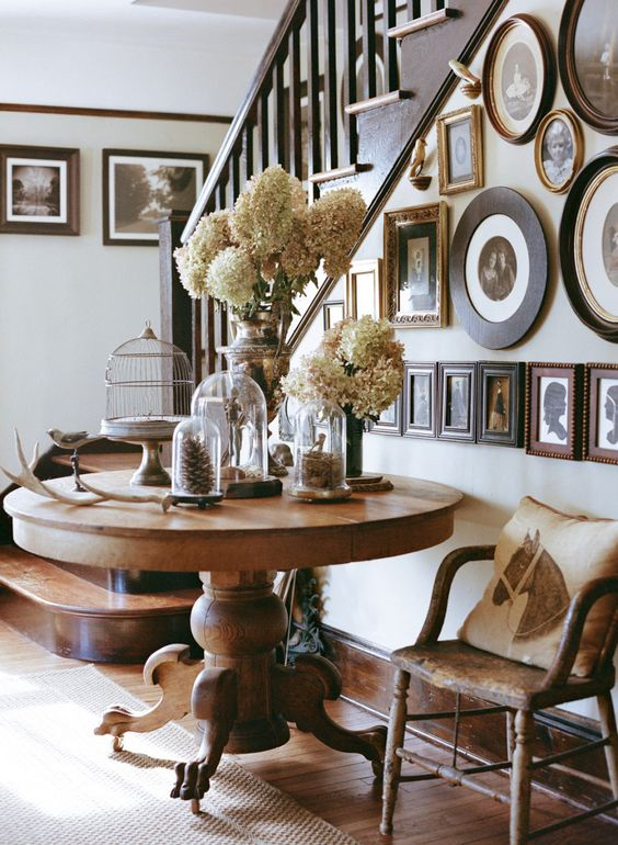 a large rustic wooden pedestal table with a fall display and a galery wall on the stairs