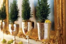 15 a mantel display with little evergreen trees in gold goblets and small apples