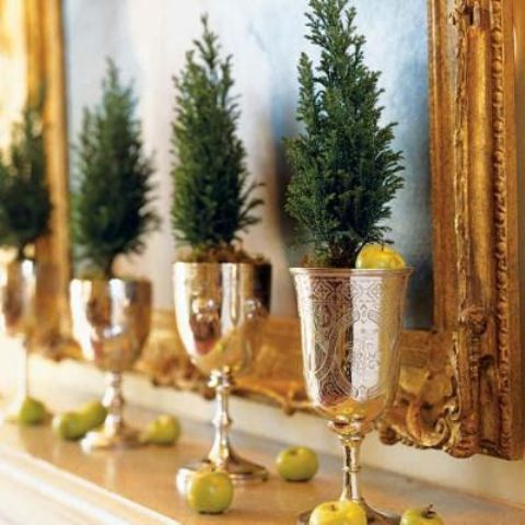 a mantel display with little evergreen trees in gold goblets and small apples