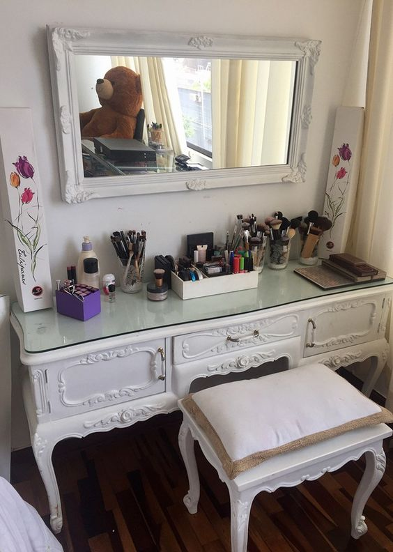 a mirror in a vintage white frame matches a vintage vanity made of a dresser