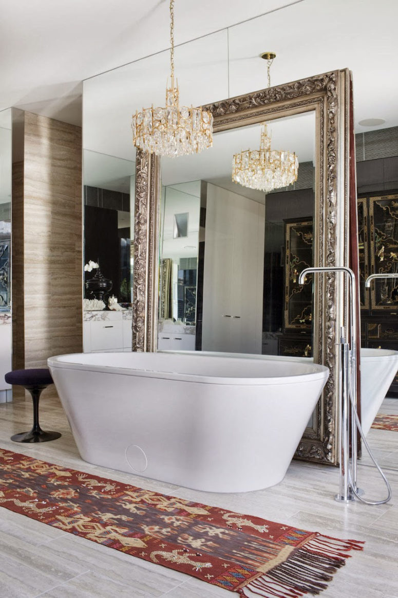 a mirror wall, an additional vintage mirror next to it and a glam chandelier over the bathtub