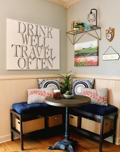 a small and cozy breakfast nook with a round table and an upholstered bench with storage crates