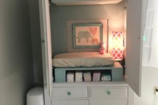 15 an armoire hides a changing table, storage and some additional light and makes the room look neat