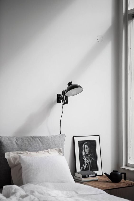 an industrial black wall sconce for a Scandinavian bedroom