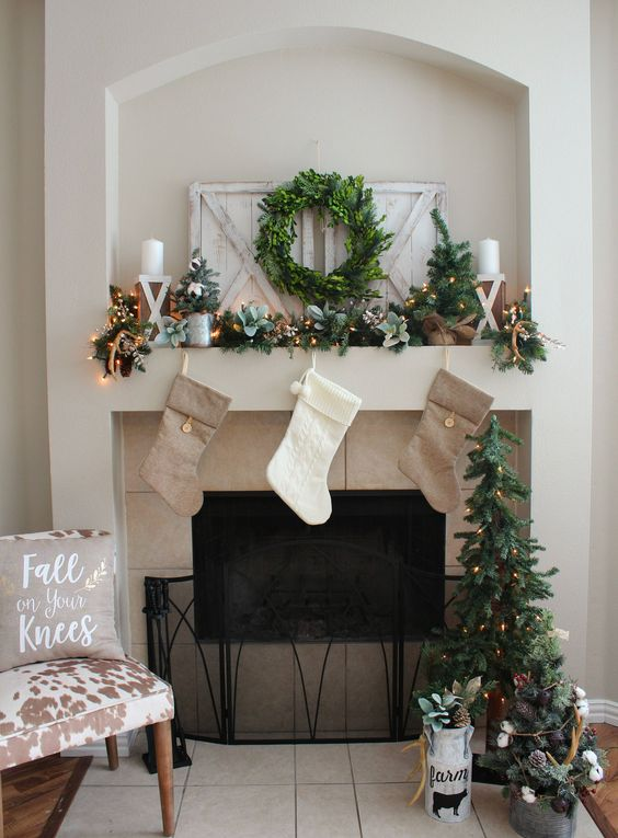 neutral stockings, an evergreen garland with lights, a wreath and some candles for pretty styling with a rustic feel