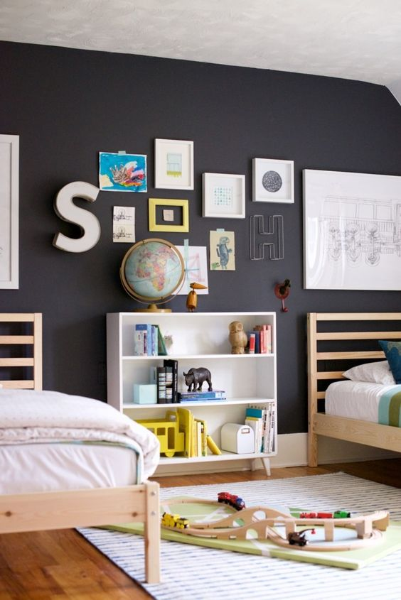 a black wall enlivened with colorful artworks and letters is great for any kids' space