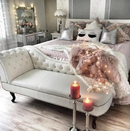 a creamy leather bench and a dusty pink faux fur blanket, a mirrored vanity and sequin pillows
