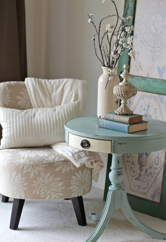 a light blue pedestal table with a drawer as a side table for a shabby chic space