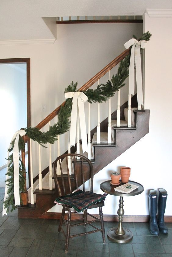 a lush evergreen garland with chic creamy ribbon bows to decorate the staircase