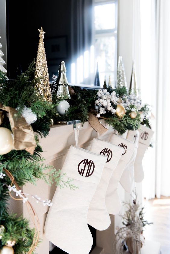 a mantel done with a faux fir garland and metallic Christmas trees in silver and gold