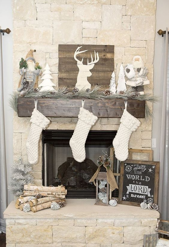 a pine garland with snowy pinecones, a pallet deer sign, Santa Claus dolls and white stockings