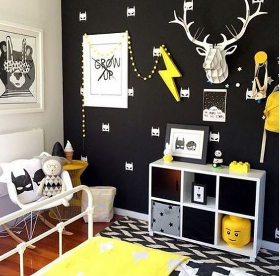 a black wall with a Batman print is made vivacious with yellow touches and artworks
