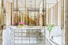 17 a built-in mirrored vanity with many drawers and marble and brass all over for a glam feel