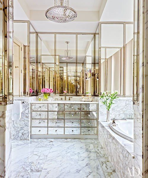 a built-in mirrored vanity with many drawers and marble and brass all over for a glam feel