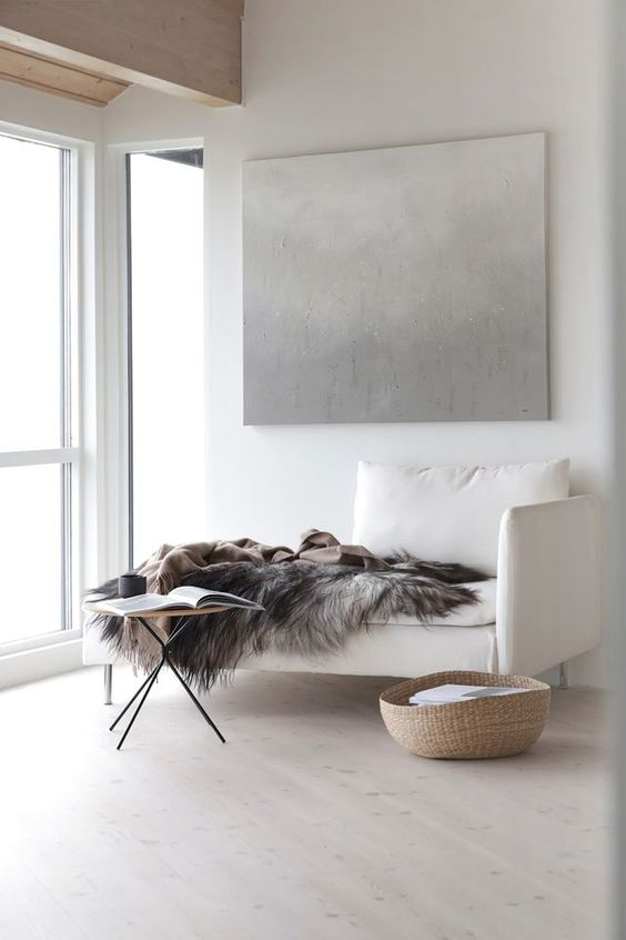 a cozy reading nook with a cremay upholstered daybed and a small table