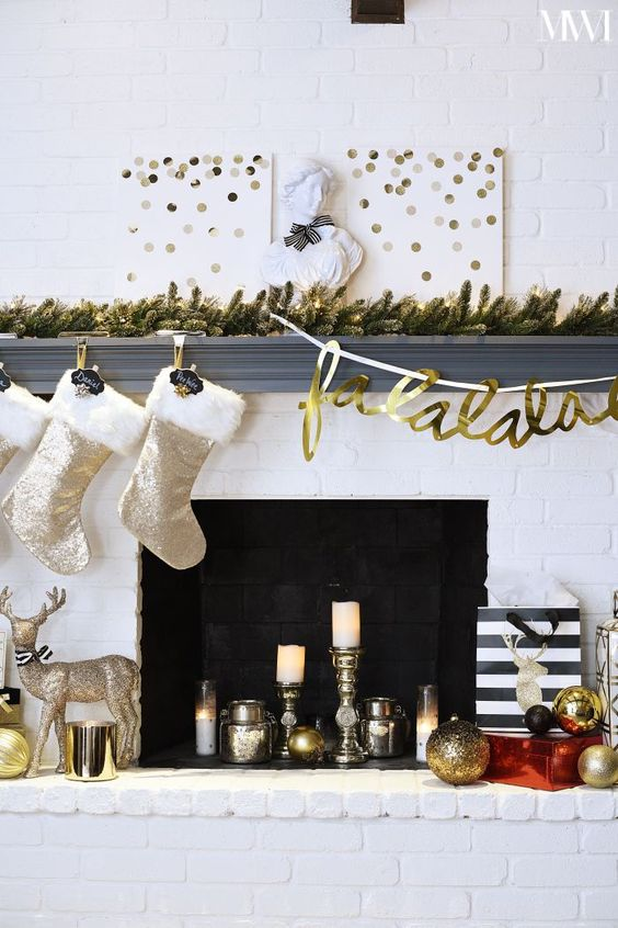 a fun glam mantel with a lit up fir garland, polka dot signs, shiny stockings, metallic decor and a sparkling deer