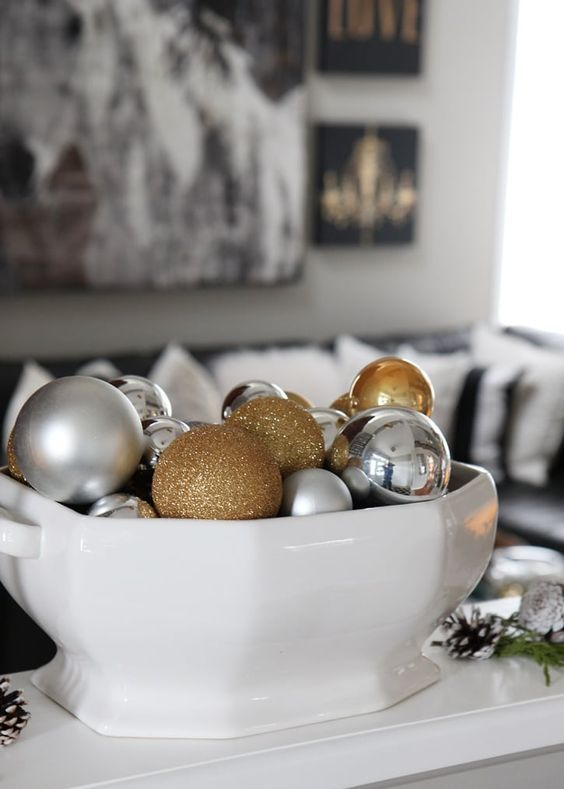 a large soup bowl filled with silver, gold and gold glitter ornaments for Christmas