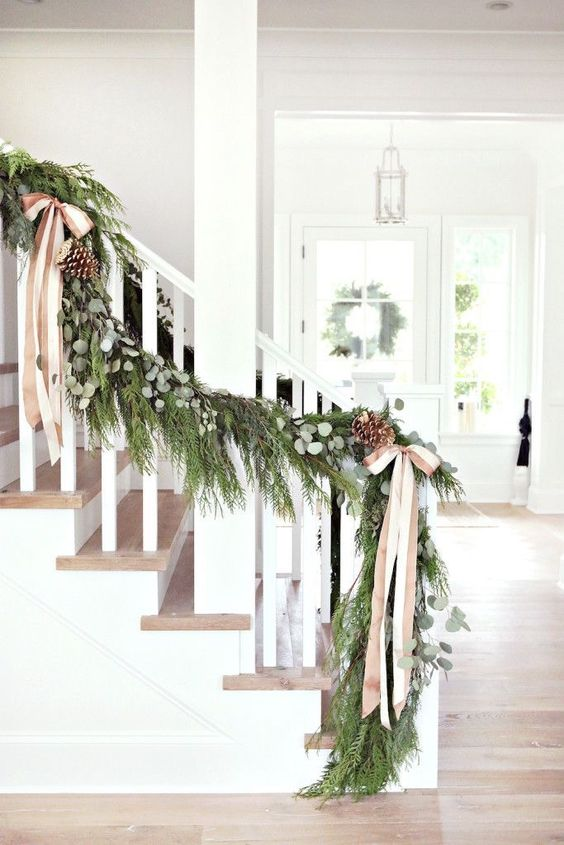 a lush evergreen garland with eucalyptus, pinecones and striped ribbon bows to decorate the stairs