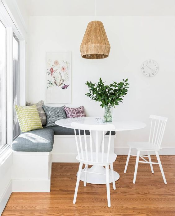a simple and cute breakfast nook with an upholstered bench, a round table and chairs