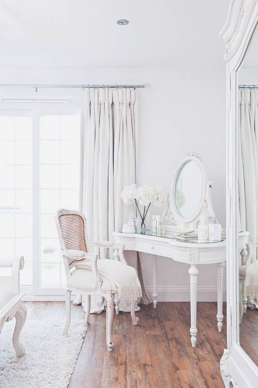 an exquisite mirror in a white frame on a matching refined vanity for a vintage space