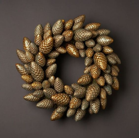a Christmas wreath of gold pinecones looks glam and chic