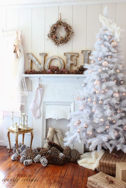 a faux mantel decorated with wooden letters, lots of pinecones and a vintage-inspired wreath over it