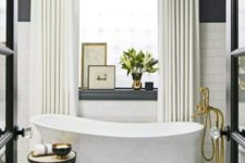 18 a free-standing bathtub on brass clawfeet and a crystal chandelier over it