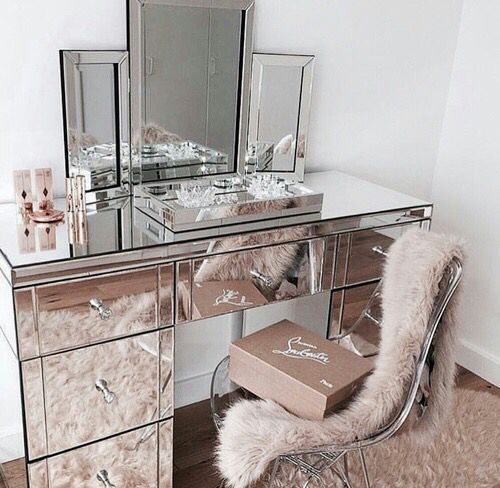 a mirror vanity and a three-part mirror on the vanity for a glam look