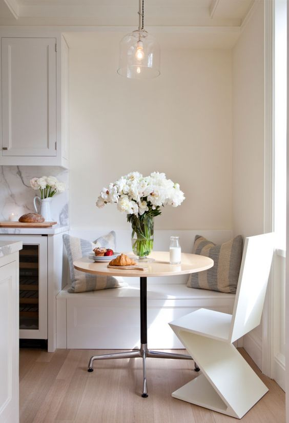 a tiny breakfast nook with a built-in bench, a round table and a geometric chair