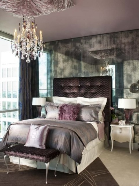 a chocolate upholstered bed and ottoman and a crystal chandelier to make the space girlish