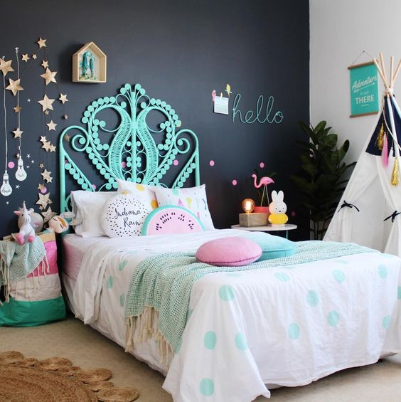 a colorful girl's space is made more peaceful with a black headboard wall