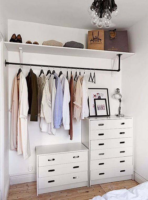a makeshift closet with chests of drawers and open shelving in the bedroom