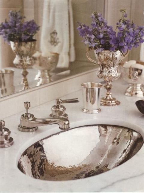 a marble countertop and a shiny silver sink with matching faucets looks very feminine, refined and chic